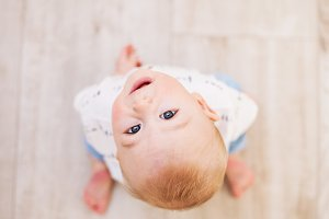 A baby boy on the floor at home, looking up. Copy space.