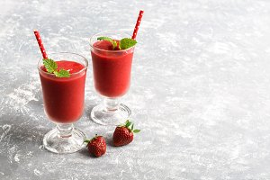 Two strawberry smoothies on a gray background. Copy space, selective focus.