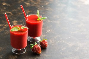 Two glasses of strawberry smoothies on a dark background. Copy space, selective focus.