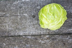 Fresh raw cabbage on wooden table.