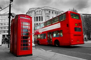 Red phone booth & red bus in motion