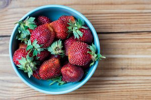 Plate of ripe juicy strawberries on rustic background