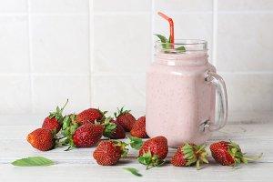 Strawberry milkshake with the scattered ripe berries