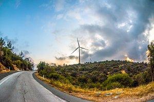 Wind farm on mountain road sunset