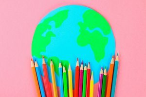 World art. Planet Earth and pencils, brushes on a pastel pink background.