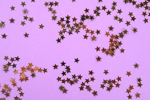 Pastel background decorated with shiny decorative stars and balls.