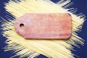 Wooden board, spaghetti on dark