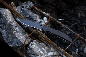 Knife on the background of rusted reinforcement. Black knife on black stones.