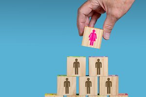 Male hand placing female leader at head of organization
