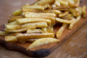 Side view of french fries on wooden