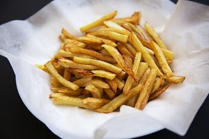 Plate of french fries on dark