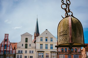 Weight of old Crane hanging in front of facade of historical buildings in Harbor Lueneburg, Lower Saxony,Germany