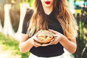 the girl is holding a burger with a stuffing. cheese, meat, lettuce, cutlets, cucumbers, sauces. Street style. summer. food
