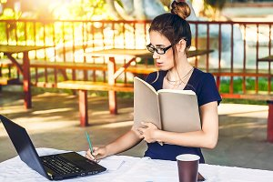 the girl is working in the fresh air for a laptop. holds a notebook in his hands for notes. a glass of hot drink. glasses for protection. sunny day. work, internet, study.