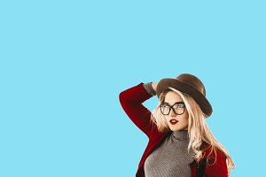 Blonde with curly hair, hat on her head with red lipstick on her lips. . I put on glasses transparent image. turquoise background. pastel color