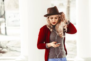 the girl straightens her hair. listening to music on headphones. hat on the head. street walk. communication on the phone.