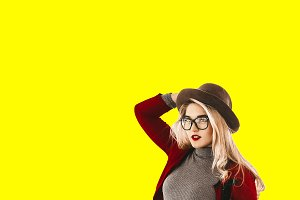 beautiful girl. yellow background. hat on the head. stylish glasses with a transparent frame. red lipstick on the lips.