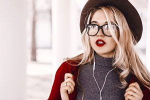 the girl in a hat and transparent glasses listens to music. surprised. emotions of the girl. Red lipstick