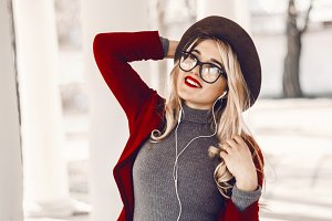 happy girl listening to music for mood with headphones. Hat on head and transparent glasses
