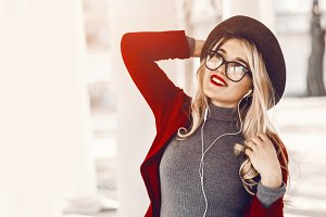 the girl listens to joyful music in the headphones. good mood. hat on the head. glasses. smile and happiness