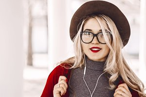 blonde happy. red lipstick and transparent glasses, hat. portrait of a girl.listening to music