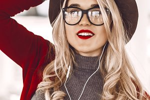 the girl listens to the cheerful music in the headphones. hat on head, red lipstick on lips