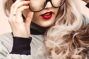 Portrait of a girl. curly hair. Blonde with painted lips and in image glasses