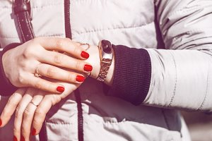 Pedometer on the hand of the girl. a gold bracelet. red nails