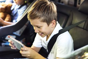 Boy playing on a smartphone in car