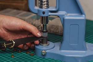Tanner puts rivets on leather