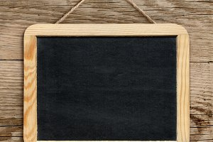 Blackboard hanging on wooden wall