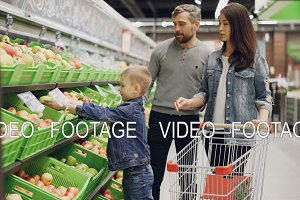 Young family with child is shopping for food in supermarket, parents are choosing fruit and boy is putting them in shopping cart. Grocery store and family life concept.
