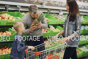 Father, mother and child are choosing pineapple in grocery store touching and smelling it showing thumbs-up. Shelves with delicious fruit and shopping trolley are visible.