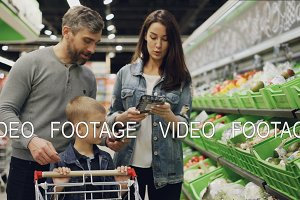 Handsome bearded guy, his attractive wife and cute child are choosing vegetables in trays in supermarket, talking, laughing and putting products in trolley.