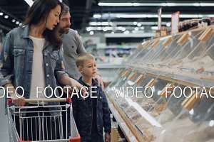 Mother, father and their son are shopping for food in supermarket pointing at plastic boxes on shelves and talking. Large food store and its employees are visible in background.