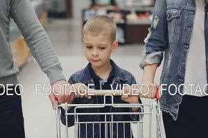 Adorable child is pushing shopping trolley inside food store, his loving parents are helping him. Children, young family, supermarket and daily routine concept.