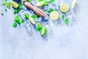 Summer drink header with mojito cocktail ingredients, mint, lime and ice cubes. Lemon reamer or juicer on a gray stone background with copy space.