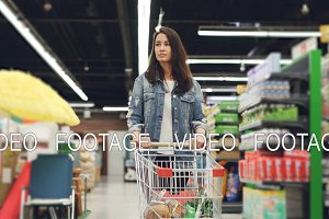 Dolly shot of pretty young lady with shopping cart walking along rows of shelves with products and looking around with smile. Shopping for food and people concept.