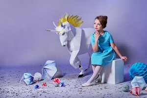 Dreamy,romantic little girl lady sits amid origami studio,white big unicorn,diamonds, geometric shapes. Beautiful,refined child in designer blue dress for holiday.Charming elegance teenager woman.