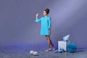 Beautiful,refined girl,designer turquoise,blue dress for holiday.Charming elegance teenager woman,studio gray,lilac background,ray light,empty space.Attractive female pointing finger copy space.