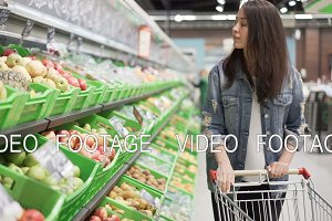 Pretty young woman is choosing fruit in grocery store, she is touching and smelling apples then putting them in trolley. Healthy food, beautiful girls and shops concept.