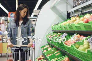Charming girl in casual clothing is walking along fruit row moving shopping trolley and looking at organic fruit with smile. Healthy lifestyle and supermarket concept.
