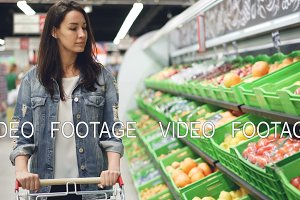 Pretty young woman is walking along fruit and vegetable row pushing shopping trolley and looking at organic food with smile. Healthy lifestyle and supermarket concept.