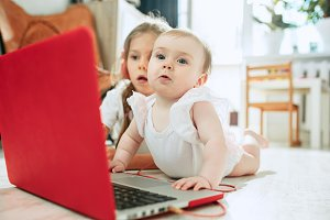 Portrait of little baby girl looking at camera with a laptop