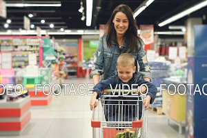 Joyful loving mother is having fun in supermarket with her cute little son, she is running with shopping cart with small boy standing on it, people are laughing.
