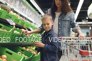 Cute blond boy is shopping with his mother buying fruit, he is taking apple from plastic box and putting it in trolley, his mom is smiling and talking to her son.