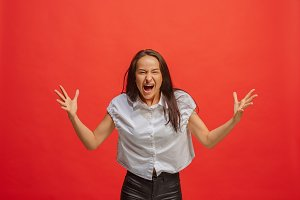 The young emotional angry woman screaming on red studio background