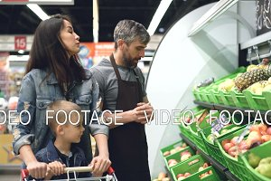 Sociable handsome shop assistant is selling fresh fruit to attractive young woman with child, man is pointing at bright boxes with products and speaking.