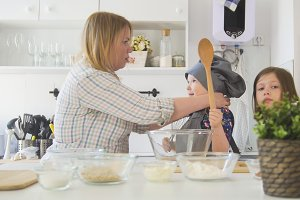Mom puts a hat on her little girl who holding a wooden spoon in hand and elder girl looking at camera in a cooking studio