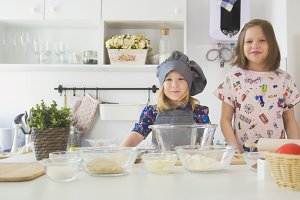 Portrait of little sisters preparing for cooking at studio